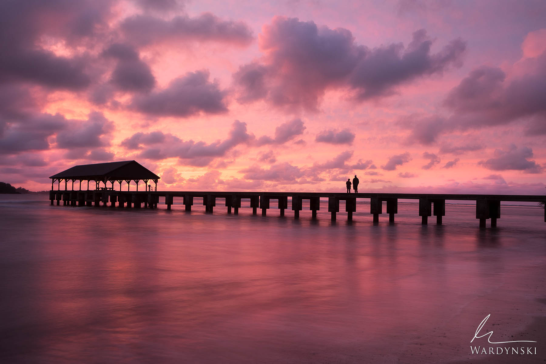Fine Art Print | Limited Edition of 50  A couple watches a pink cotton candy sunset from the Hanalei Bay Pier on the island of...