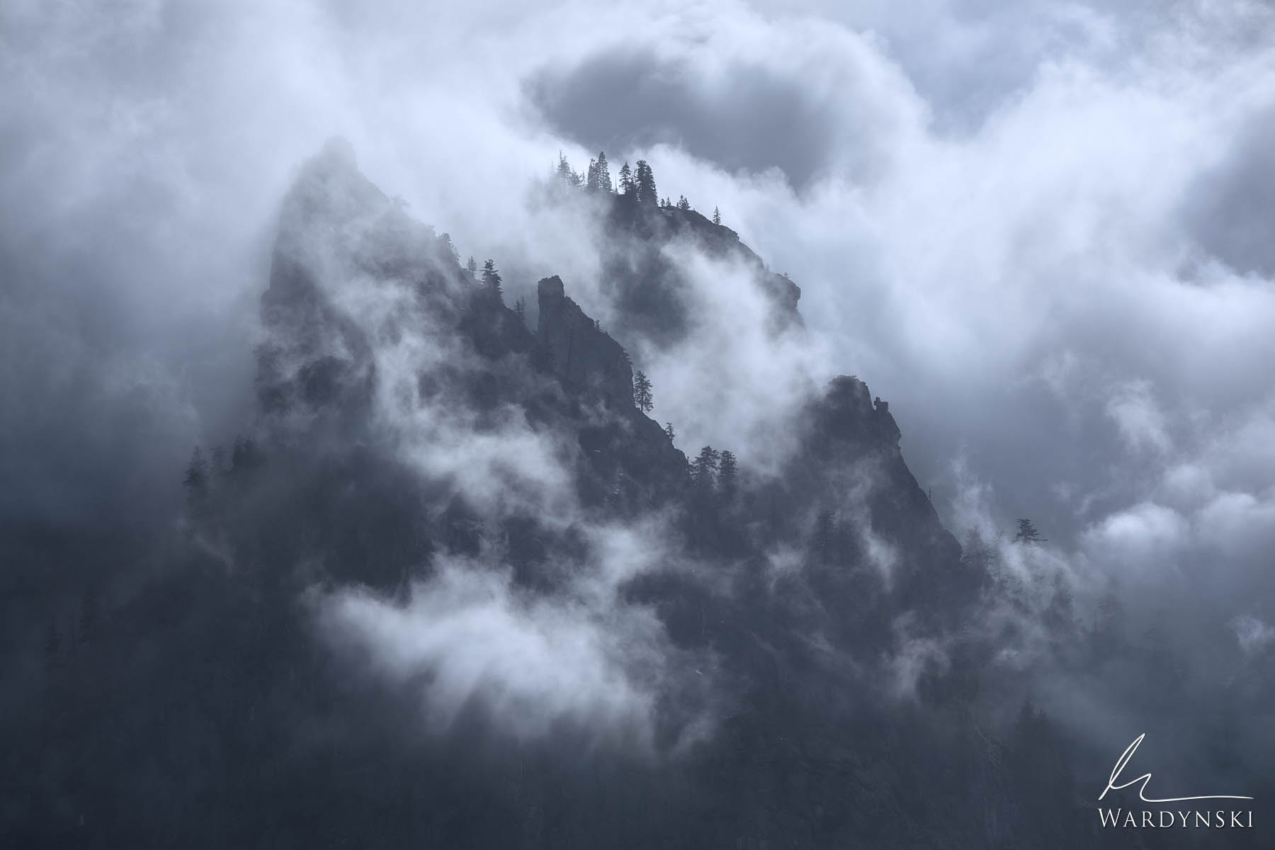 Fine Art Print | Limited Edition of 100  Granite spires rise through the fog and clouds in Yosemite Valley. This moody blue landscape...