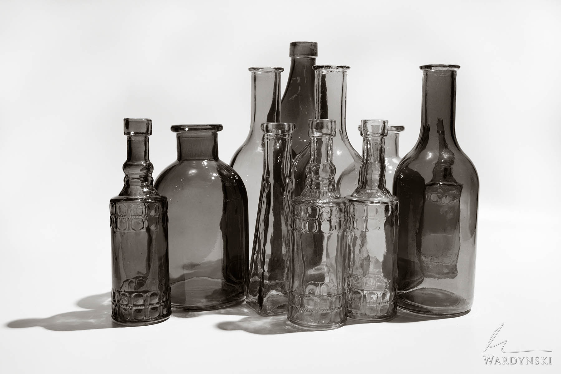 Fine Art Print | Limited Edition of 25 Light travels through multi colored glass bottles in a sepia tone minimal photograph. ©...