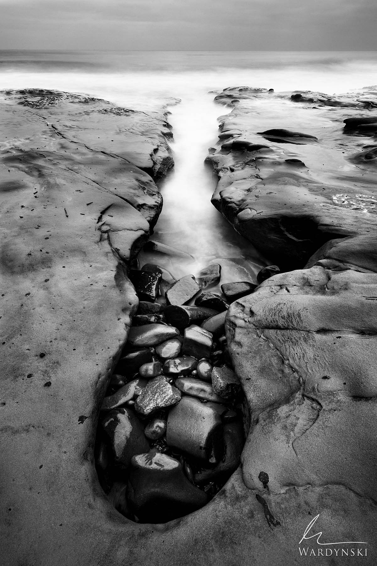 Black and White Fine Art Print | Limited Edition of 100  A collection of rocks rest in a sandstone trough along the shores of...
