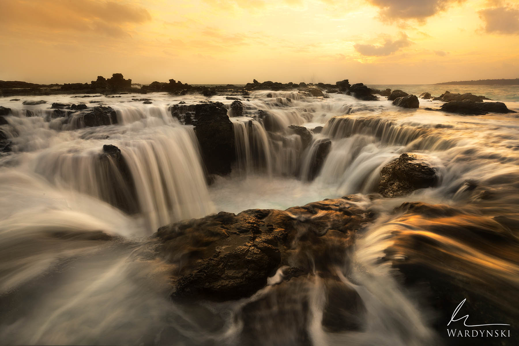 Fine Art Print | Limited Edition of 50  A cascade of water pours into an ancient lava tube on the coast of Kauai. During high...