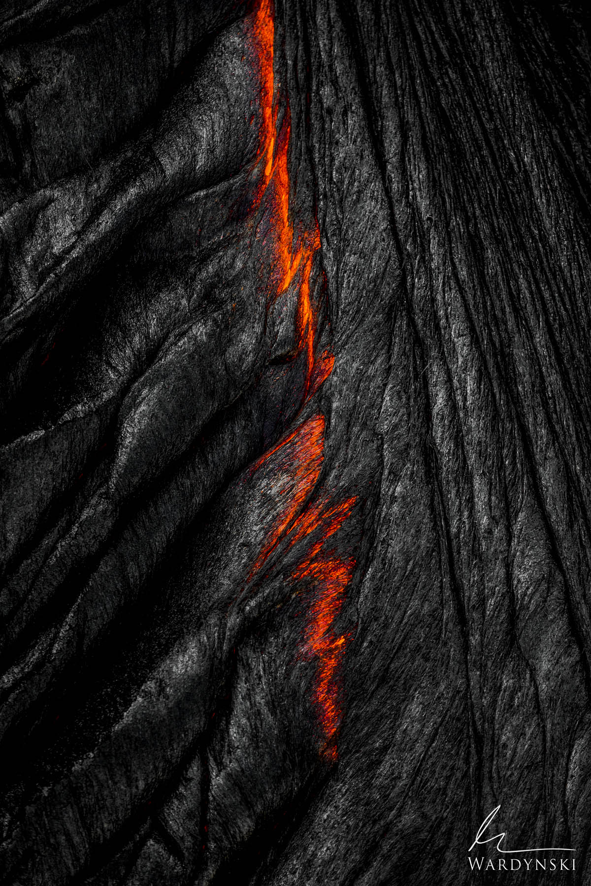 Fine Art Print | Limited Edition of 50  A red rift forms on hardened black lava rock as the molten lava below makes its way to...