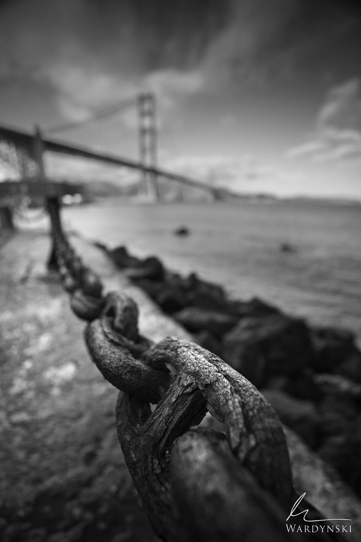 Black and White Fine Art Print | Limited Edition of 50  Large heavily corroded chains hang in front of the Golden Gate Bridge...