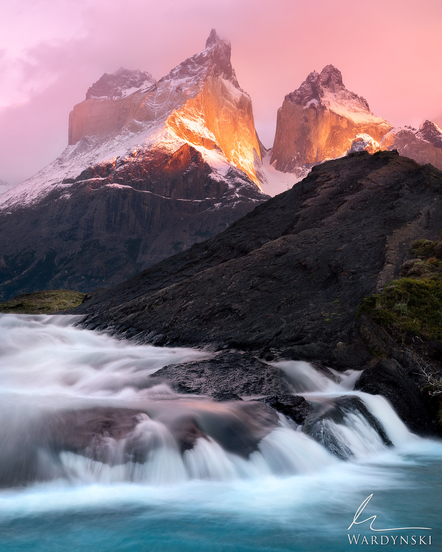 Fine Art Print | Limited Edition of 100  A beam of warm light strikes Cuerno Del Paine during a particularly windy sunrise in...