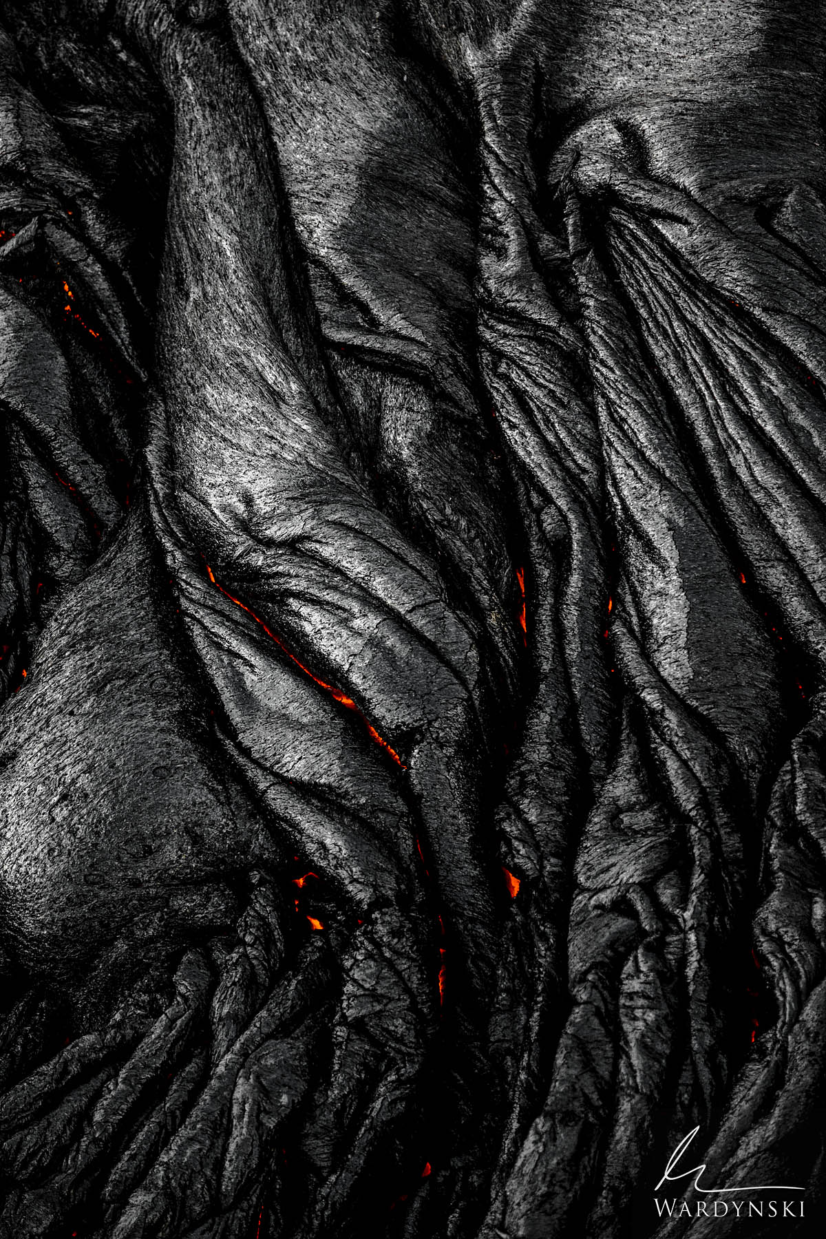Fine Art Print | Limited Edition of 25  Hot lava can be seen just beneath the surface of freshly cooled black rock. The folded...